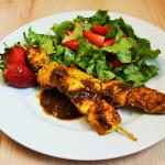 Asiatische Hühnerspieße auf Salat mit Erdbeeren